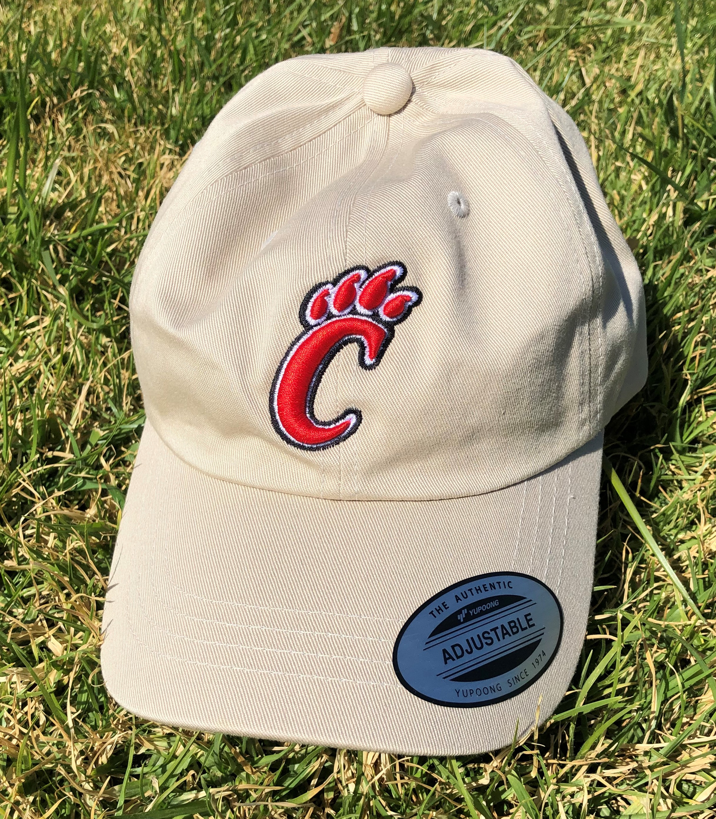 tan baseball cap with C paw print logo